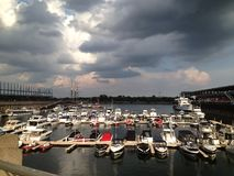 Yachts and boats moored in a marina. Under dark, dramatic sky at Old Port of Montreal Stock Image