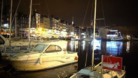 Yachts and boats moored to shore in city harbor at night, illuminated embankment. Stock footage stock footage