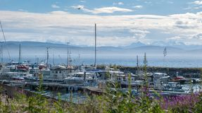 Yachts and boats on a mooring on a background of cloudy sky and mountains. Norway Royalty Free Stock Photos