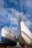 Yachts. In the boatyard set against a vibrant blue sky Stock Photography