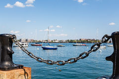 Yachts in Boston Harbor Beyond Black Chain and Bollard Royalty Free Stock Image
