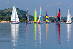 Yachts with colorful sails. Sailboats with colorful sails near the mountain royalty free stock photography