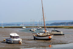 Yachts and craft beached on a tidal inlet Stock Image