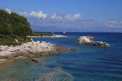 Yachts crossing horizon. Near Giaos, Paxos, Greece. Clear sea with bleached rocks and trees. Yachts passing in distance. Calm stock photography
