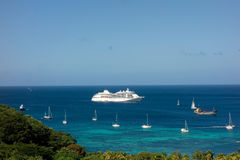 Yachts and a cruise ship at admiralty bay, bequia. Vessels anchored in a sheltered bay in the grenadine islands Stock Images