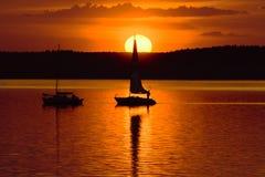 Yachts dans le lac au coucher du soleil Photos stock