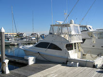 Yachts docked at a pier. With blue sky stock image