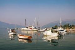 Yachts et bateaux de pêche sur l'eau un matin brumeux Baie de Kotor, Tivat, Monténégro Photographie stock libre de droits