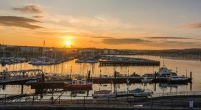 Sunrise Luxury yachts and boats moored in sea port Plymouth. Yachts and fishing boats on the water near seaside village of Plymouth Devon UK. on a early foggy royalty free stock photo