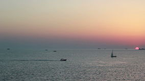 Yachts float at sunset by sea stock video