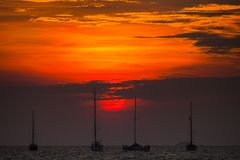 Yachts are floating on sea under vivid colorful sky at sunset timing. On sea located at south of Thailand royalty free stock photos
