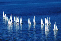 Yachts on the high seas. Several yachts sailing across the calm high blue sea Royalty Free Stock Photos
