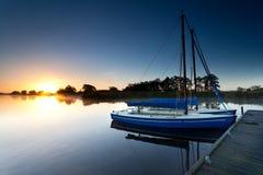 Yachts on lake pier at sunrise Stock Image