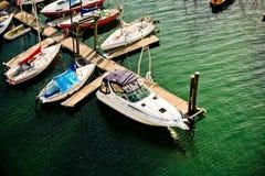 Yachts at a Marina. Yachts and sailboats docked at a marina. Green sea water Stock Image