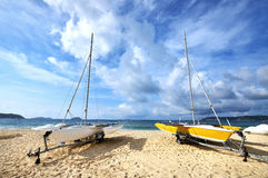 Yachts moored on beach. Two yachts moored on idyllic beach with blue sky and cloudscape background Royalty Free Stock Photos