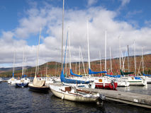 Yachts moored on lake. Yachts moored on Mercier lake marina with Autumnal forest on Mont-Tremblant mountainside in background, Quebec, Canada stock photography