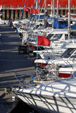 Yachts moored in a marina. Yachts and motor boats moored in a marina stock image