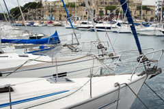 Yachts moored at Msida Marina in Malta. Sail boats in a row on docks at seaside harbor Royalty Free Stock Photos
