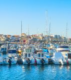 Yachts moored in Peniche marina. White yachts and motor boats moored by pier in marina, Peniche, Portugal royalty free stock photo