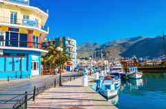 Yachts moored in port colorful buildings, Greece Stock Photos