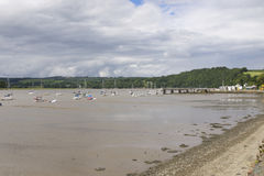 Yachts moored in River Tamar close to Weir Quay. Yachts moored on River Tamar near Weir Quay with mud shore, on cloudy day royalty free stock photography