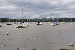 Yachts moored in River Tamar. Yachts moored on River Tamar near Weir Quay with mud shore, on cloudy day stock photography
