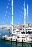 Yachts moored in Vittoriosa marina, Malta. Yachts moored in the marina with views towards waterfront buildings and Fort St Angelo, Vittoriosa, Malta, Europe Royalty Free Stock Images