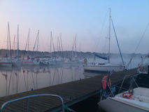 Yachts at a mooring in the early morning. Yacht at a mooring in the early morning with fog and sunrise Royalty Free Stock Photo