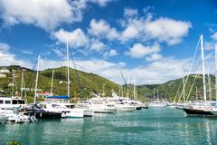 Yachts at mooring in sea in Road Town, UK. Yachts at mooring in sea on mountain landscape on cloudy blue sky background in Road Town, UK. Summer vacation and Stock Images