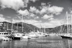 Yachts at mooring in sea in Road Town, UK. Yachts at mooring in sea on mountain landscape on cloudy blue sky background in Road Town, UK. Summer vacation and Stock Photography