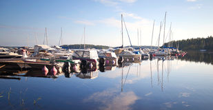 Yachts and motorboats moored in small marina Royalty Free Stock Photo