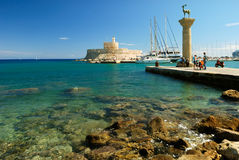 Yachts and old lighthouse in the harbor. Yachts, medieval statue of deer and old lighthouse in the harbor of Rhodes stock images