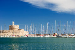Yachts and old lighthouse in the harbor. Of Rhodes royalty free stock photography