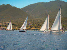 Yachts passing by the coast. With high mountains Royalty Free Stock Photo