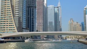 Yachts and pleasure boats are floating in Dubai in sunny weather, modern bridge. And skyscrapers are in background stock footage