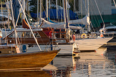 Yachts and pleasure boats parked with anchor in the harbour. Stock Photos