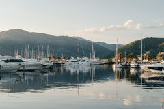 Yachts are preparing to sail in port at sunset on background of Stock Photos
