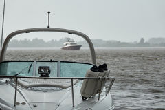 Yachts on a river in heavy rain Stock Photo
