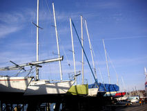 Yachts in a row. A row of yachts with tall masts stock image