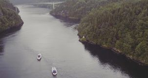 Yachts sail to bridge over fjord forestry hilly banks stock footage