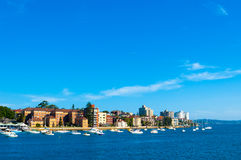 Yachts and sailboats anchor along the city's shore under clear b Royalty Free Stock Images
