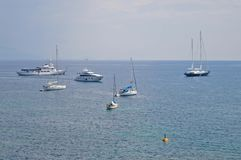 Yachts and sailing-boats in the bay of Corfu town. Several yachts and sailing-boats are standing on the sea, in the bay area of Corfu, with the horizon in the Stock Photo