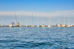 Yachts and sailing boats are on the dock. The small naval vessels are in the harbor on a background of blue sky Royalty Free Stock Image