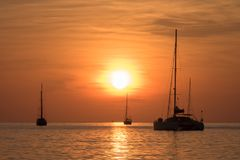 Yachts in the sea at sunset. Three yachts in the sea at orange sunset stock photography