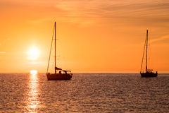 Yachts in the sea at sunset Royalty Free Stock Photos