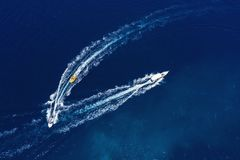 Yachts at the sea surface. Aerial view of luxury floating boat on transparent turquoise water at sunny day. Top view from drone. S. Eascape with motorboat in bay stock photography