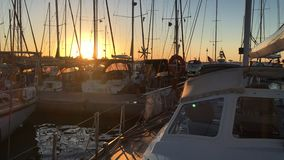 Silhouettes of Sailboats Docked in Port in Dusk. Yachts Silhouettes With Masts, Shruds, Spreaders, Pulpits, Booms, Rigs in the Sunset Light in a Summer Evening stock video footage