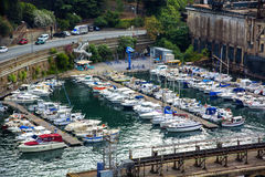 Yachts in Small Marina by Road in Industrial Area Stock Photo