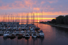 Yachts in the Sunset. Spectacular sunset casts the perfect glow on the water. Sunset with silouetts of masts and reflections Royalty Free Stock Images