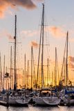 Yachts at sunset at the Ala Wai Small Boat Harbor in Honolulu, Hawaii. Small plane flying over yachts at sunset at the Ala Wai Small Boat Harbor in Honolulu stock photography